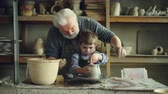 forming : Concentrated young boy is molding clay into ceramic vase on spinning throwing wheel and his experienced grandfather is helping him. Pottery and family tradition concept.
