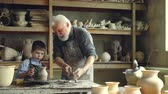 louça de barro : Professional potter is cutting ceramic pot from throwing wheel and his little grandchild is bringing it to work table. Family members working together concept.