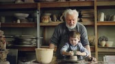 molding : Concentrated child is forming pot from clay on potters wheel under guidance of his experienced grandfather. Ceramic pots, vases and figures are in background. Stock Footage