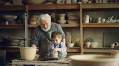 forming : Elderly man experienced potter is teaching little boy how to work with clay on potters wheel. Sharing experience, family tradition and modern pottery concept.
