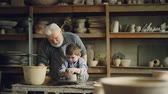 forming : Caring grandfather experienced potter is teaching little boy how to work with clay on potters wheel. Grandson is making mistake, patient grandpa is helping him.