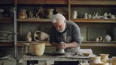molde : Hardworking grey-haired man is working with clay on potters wheel, shaping piece of loam. Beautiful ceramic utensils, handmade pots and vases on shelves are visible.