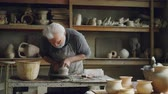 mistr : Experienced ceramist is creating utensils from clay on throwign wheel in workshop. Producing eathenware, handmade utensils and professional pottery concept. Dostupné videozáznamy