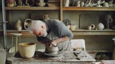 tekerlek : Skilled elderly potter is producing ceramic pot on turning wheel in workplace. Creation process, traditional pottery and interesting hobby concept. Stok Video