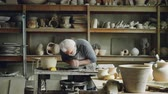 loam : Hardworking silver-haired man is working with clay on potters wheel, shaping piece of loam. Beautiful ceramic utensils, handmade pots and vases on shelves are visible.