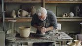 molde : Creative senior potter is wetting hands in bowl with water and touching piece of clay on spinning throwing-wheel. Bearded man is concentrated on work. Vídeos
