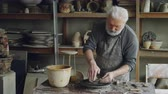 forming : Creative male potter is forming unsymmetrical broad bowl on throwing wheel while working in small workshop. Creativity, pottery and unusual hobby concept. Stock Footage
