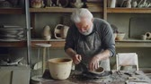 loam : Creative sculptor is making unusual broad bowl while standing at working table in his workshop. Bearded senior man is liiking at his clayware and appraising design and quality.