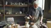 forming : Professional male ceramist is kneading clay, forming clay ball while working in small workshop with potters equipment, tools and many ceramic figures. Stock Footage