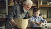 forming : Concentrated young boy is molding clay into ceramic pot on spinning throwing wheel and his experienced grandfather is talking to him. Pottery and family tradition concept.