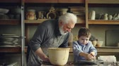 forming : Pottery teacher senior adult is helping young student to form pot from piece of clay on throwing-wheel. Cute boy is awkward, and craftsman is helping him. Stock Footage