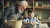 forming : Caring grandfather is watching his grandchild molding clay on throwing wheel, making low ceramic vase then washing hands in large bowl. Pottery and family concept. Stock Footage