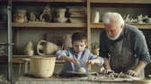 molding : Retired grandfather giving basics of pottery to his cute little grandson while working together in cozy home workshop. Making ceramics and family concept.