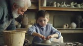 curiosidade : Little boy pottery learner is creating clayware on throwing-wheel while his experienced grandgather is talking to him and helping him. Making ceramics and family concept.
