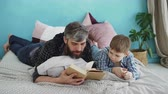 parente : Bearded man is reading book to his little son lying on bed in nice cozy bedroom. United family, spending leisure time and raising children concept. Vídeos