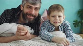 parente : Close-up portrait of two people adult father and cute little son lying on bed at home and smiling. Paternal love, parenthood and happy family concept.