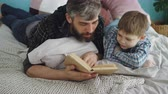 parente : Loving parent bearded man is reading interesting book to his curious little son on double bed at home. Parenthood, happy people, love and family concept.