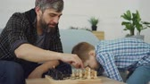chess board : Loving dad is playing chess with his little child, teaching him rules and talking to him. Raising children, intellectual games and happy childhood concept.