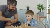 teach : Serious preschool child is playing chess with his parent thinking about next move and moving chesspieces while his father is teaching him game tactics.