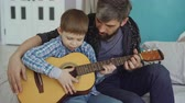 teach : Concentrated child is playing guitar with his father experienced guitarist, adjusting musical instrument and enjoying happy moments. Music and family concept. Stock Footage