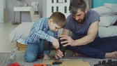 pistola : Careful father is teaching his son to work with electric screwdriver while son is trying to use screw gun and fix screw in pieces of wood. Construction and family concept.
