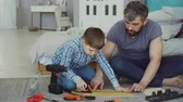 правитель : Little boy is learning to use measuring reel while doing construction work with his father, while dad is explaining basics of repair and construction.