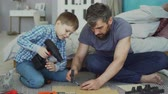 ajudar : Little boy is learning to use electric screwdriver while his dad is explaining how to work with screw gun and fix screw in piece of wood. Construction and family concept.