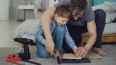 nehty : Father bearded man is teaching his son how to use hammer driving nail in piece of wood together sitting on floor at home. Instruments, tools and furniture are visible.
