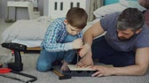 srubokręt : Curious child is driving screw in piece of wood with screwdriver and his dad is holding wooden sheet and teaching him basics of woodwork. United family concept.