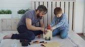 madeira compensada : Helpful son is sawing sheet of wood with hand saw while his father is measuring cut with measure-reel and talking to his child. Construction, united family and childhood concept.