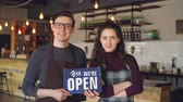 começo : Cheerful attractive people coffee-house owners are holding we are open sign while standing inside coffee shop. Opening new business and people concept.