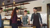 local : Young people are buying coffee-to-go in nice local cafe and paying with smartphone while friendly workers are greeting customers and selling drinks. Vídeos