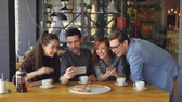 long distance : Young people are having video chat holding smartphone looking at webcam chatting to friend at table inside nice cafe. Modern communication and friendship concept. Stock Footage