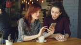 wi fi : Pretty young girl is using smartphone and showing interesting photos to her female friend the discussing them while drinking coffee in nice modern cafe. Stock Footage