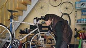 mestre : Handsome male mechanic is repairing wheel of bicycle with professional tool while working alone in small workshop with equipment and spare parts visible.