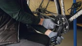 mistr : Close-up shot of strong male hands in protective gloves repairing broken bicycle treadle tightening joint with allen wrench in nice cozy workplace.