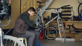 мастерская : Experienced master is repairing bicycle treadle with special tools key wrench while working in workshop with spare parts and equipment. People and maintenance concept. Стоковые видеозаписи