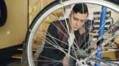 cyklus : Young man experienced serviceman is fixing bike wheel using wrench and tools. Small cozy workshop interior with wooden walls and ladder, spare parts and equipment are visible.