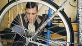 совместный : Skilled serviceman is repairing bike turning treadle and rotating wheel fixing it with wrench tightening joints. Spinning metal wheel spokes are in foreground.