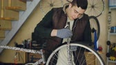 звук : Concentrated young mechanic is greasing bicycle wheel and listening to music with earphones while repairing bike in his small home studio. Maintenance and people concept.