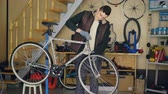 cyklus : Young maintenance man is assembling bicycle placing stearing wheel and fixing it while listening to music with earphones in his workplace. Repair and people concept. Dostupné videozáznamy
