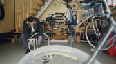 звук : Handsome mechanic is fixing back wheel with wrench while working in modern workplace sitting on wooden stool. Cycles, spare parts, tools and equipment are visible.