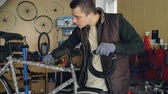 велосипед : Young mechanic owner of bike repairing workshop is fixing bicycle holding bundle of wire and fixing it to bike frame. Small business and maintenance concept. Стоковые видеозаписи
