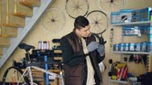 cyklus : Concentrated repairman is greasing mechanism while repairing bicycle in nice workshop. Young man in warm vest and protective gloves is listening to music .