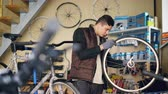 совместный : Self-employed mechanic is repairing bicycle wheel with wrenches professional instruments while working in small workshop. Young man is listening to music with earphones.