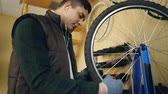 servicing : Concentrated mechanic is fixing spokes on bicycle wheel with special tools while servicing bike and listening to music through earphones. Maintenance and profession concept.