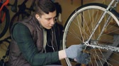állítsa : Skilled mechanic is rotating bicycle wheel checking mechanism and turning treadle while fixing bike. Professional cycle maintenance and working people concept. Stock mozgókép