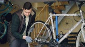 earbuds : Experienced mechanic is assembling bicycle adjusting back wheel during servicing vehicle in workplace. Professional instruments, spare parts and equipment are visible. Stock Footage