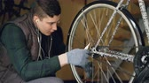 tightening : Serious guy experienced master is fixing bicycle wheel tightening mechanism joints using professional instruments. Rotating wheel with shiny metal spokes is in foreground. Stock Footage