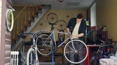 barre à roue : Experienced mechanic in casual clothes is checking handlebar and front wheel of bicycle then adjusting and fixing it with tools. Repairing cycles and people concept.